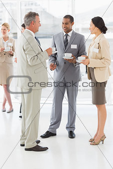 Business people talking and drinking coffee at a conference