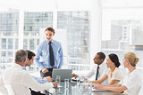 Businessman standing in front of his team at meeting