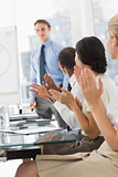 Businessman being applauded by colleagues for his presentation