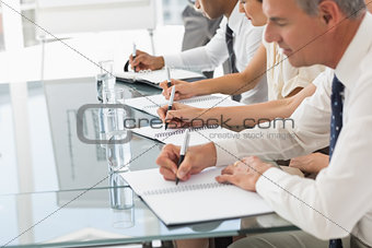 Business people taking notes at a meeting