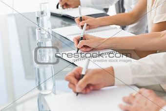 Business people taking down notes at a meeting