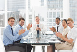 Business people clapping the camera at a meeting