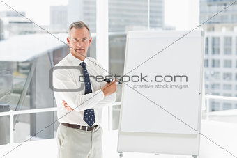 Stern businessman standing at whiteboard with marker