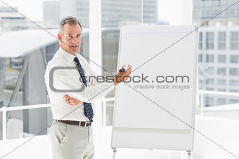 Smiling businessman presenting at whiteboard with marker