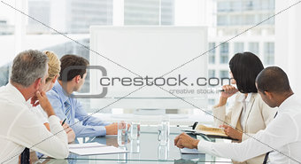 Business people looking at blank whiteboard
