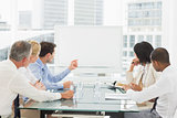 Business people looking at blank whiteboard in conference room