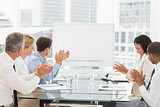 Business people clapping at blank whiteboard in conference room