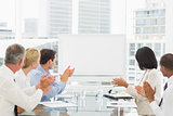 Business people applauding blank whiteboard in conference room