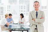 Happy businessman looking at camera while staff discuss behind him