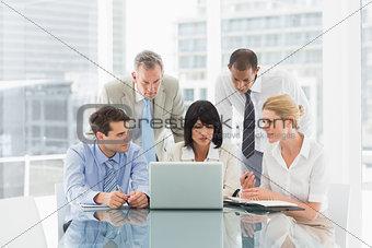 Business people gathered around laptop talking