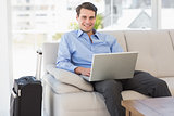 Travelling businessman using laptop sitting on the couch smiling at camera