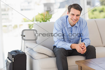 Smiling businessman sitting on couch waiting to leave on business trip
