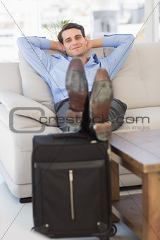 Smiling businessman sitting on couch with feet up on suitcase