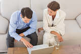 Business partners working together on laptop sitting on sofa