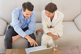 Business partners working on laptop sitting on sofa