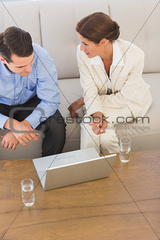 Business partners working on laptop together sitting on sofa