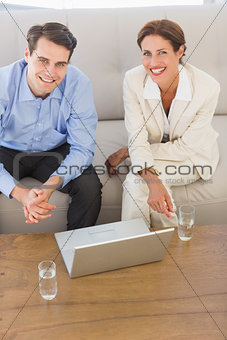 Business partners smiling at camera sitting on sofa