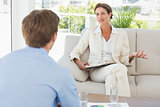 Businesswoman speaking with colleague sitting on sofa