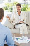Businesswoman smiling at colleague sitting on sofa