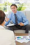 Happy businessman scheduling with colleague sitting on sofa