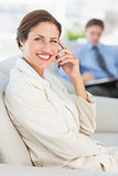Cheerful businesswoman on the phone sitting on couch