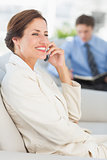 Cheerful businesswoman on the phone sitting on sofa
