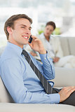 Happy businessman on the phone sitting on sofa