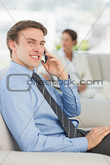 Smiling businessman on the phone sitting on sofa