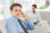 Smiling businessman on the phone sitting on couch