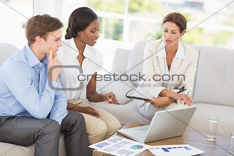 Business team meeting to go over figures on the couch