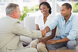 Young couple shaking hands with salesman on the couch