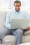 Happy businessman working on laptop on the sofa