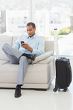 Businessman sending a text sitting on sofa waiting to depart on business trip