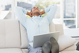 Relaxed businessman on the couch with laptop