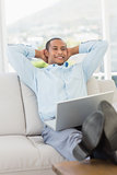 Relaxed smiling businessman on the couch with laptop