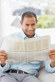 Happy businessman reading newspaper on the couch