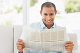 Smiling businessman reading newspaper on the couch