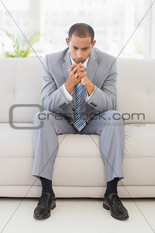 Anxious businessman sitting on couch