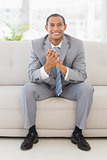 Excited businessman sitting on couch