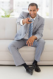 Smiling businessman sitting on couch using remote