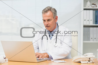 Focused doctor sitting at his desk using his laptop