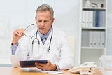 Focused doctor sitting at his desk with clipboard