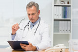 Concentrating doctor sitting at his desk with clipboard