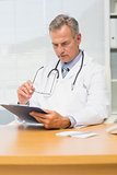 Concentrating mature doctor sitting at his desk with clipboard