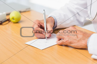 Doctor sitting at his desk writing out a prescription