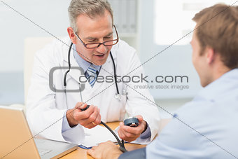 Happy doctor taking his patients blood pressure