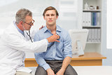 Mature doctor listening to his patients chest with stethoscope