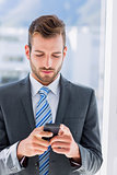 Handsome young businessman text messaging