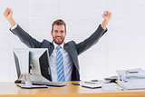 Cheerful businessman clenching fist at office desk