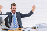 Cheerful businessman clenching fist computer at office desk
